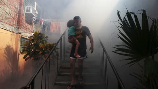 A man walks away from his home with his son as health workers fumigate the Altos del Cerro neighborhood as part of preventive measures against the Zika virus and other mosquito-borne diseases in Soyapango, El Salvador January 21, 2016.