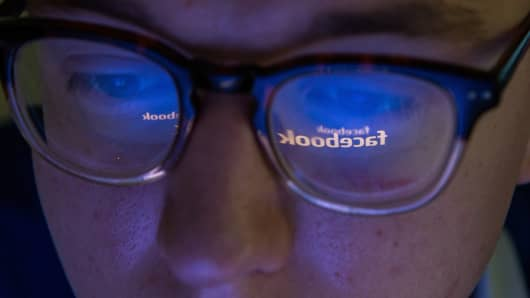 Facebook logo reflected in man's glasses
