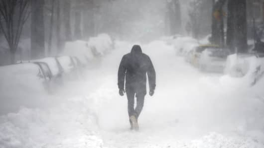 A man walks along a street covered by snow during a winter storm in Washington.