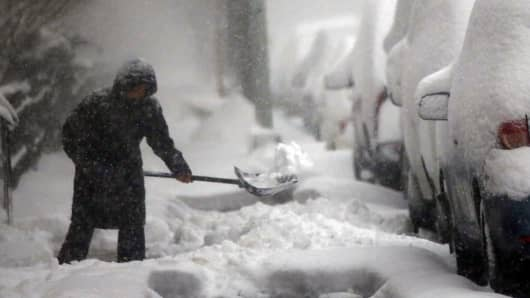 A woman shovels a sidewalk in blizzard-like conditions on January 23, 2016 in the Brooklyn borough of New York City. The Northeast and parts of the South are experiencing heavy snow and ice from a slow moving winter storm. Multiple deaths from traffic accidents have already been reported as the storm makes its way up the coast.