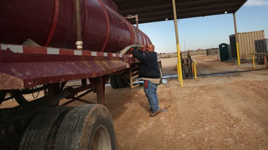 An oilfield worker fills his truck with water at a filling station before heading to a drilling site in the Permian Basin oil field on January 20, 2016 in the oil town of Andrews, Texas.