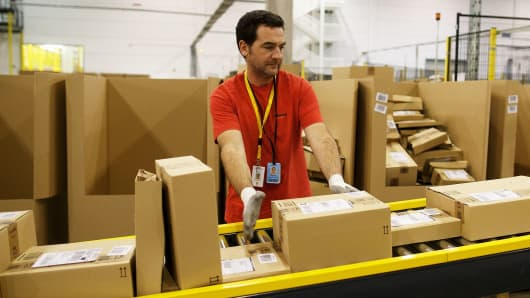 An employee collects boxes from a conveyor belt at the Amazon fulfillment center in Madrid, Spain.