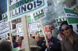 Demonstrators, protesting the state of Illinois budget stalemate, rally in the Loop before marching to the Chicago Board of Trade Building where they bolcked all of the entrances to the building on November 2, 2015 in Chicago, Illinois.
