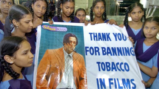 Indian school children hold a placard showing actor Salman Khan smoking, as they take part in a rally (June 2005), supporting the stand taken by India's Government which has banned smoking in films and television.