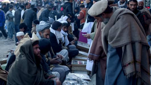 Afghan money changers wait for customers at the currency exchange Sarayee Shahzada market in Kabul on Dec. 17, 2015.