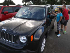 A couple checks out a Jeep Renegade for sale at the Hollywood Chrysler Jeep dealership in Hollywood, Florida.