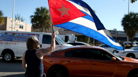 A man waves a Cuban flag as he stands outside the Little Havana restaurant Versailles, in Miami.