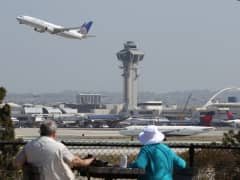 People watch as a United Airlines jet passes the air traffic control tower at Los Angles International Airport (LAX) during take-off in Los Angeles, California.