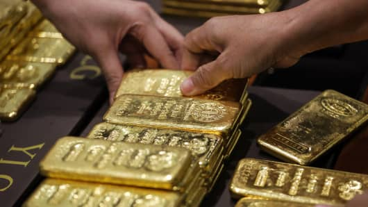 An employee arranges one kilogram gold bars for a photograph at the YLG Bullion International Co. headquarters in Bangkok, Thailand