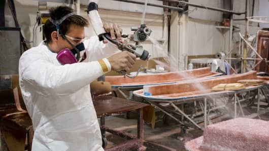 An employee sprays fiberglass over a modular boat part at the Everglades Boats manufacturing facility in Edgewater, Florida.