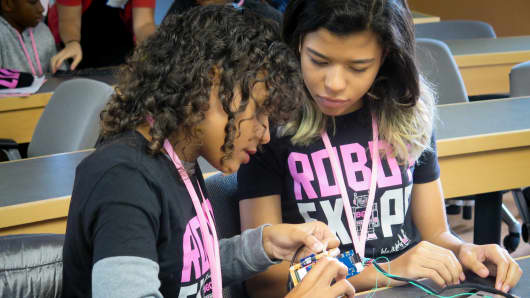 Two girls work on building a robot.
