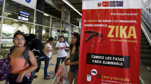 Travelers walk past a poster with information about the Zika virus during a campaign by Peru's Health Ministry at Plaza Norte bus station in Lima, Peru, on Feb. 4, 2016.