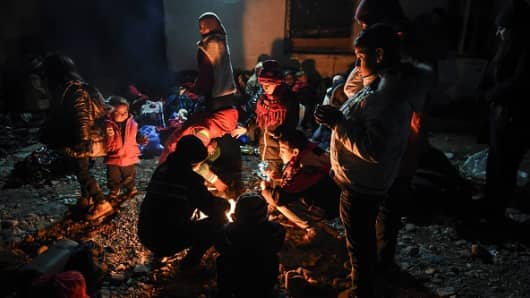 Migrants and refugees gather around a bonfire as they wait to enter the refugee camp after crossing the Greek-Macedonian border, near Gevgelija, on December 6, 2015.