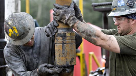 Nomac Drilling Corp. floorman steadies a section of drill pipe and cleans the connection during natural gas drilling operations for Chesapeake Energy Corp. in Bradford County, Pennsylvania.