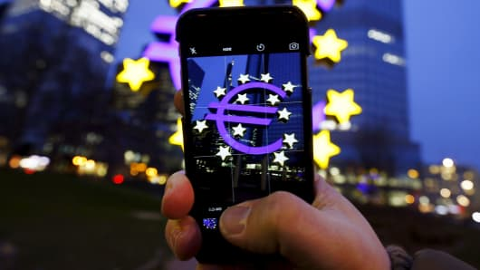 A tourist takes a picture of the euro sign landmark outside the former headquarters of the European Central Bank (ECB) in Frankfurt, Germany.