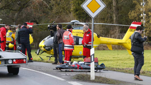 Rescuers and journalists stand in front of a rescue helicopter near Bad Aibling in southwestern Germany, February 9, 2016. Several people died after two trains collided in the southern German state of Bavaria on Tuesday, a police spokesman said, adding about 100 people were also injured.