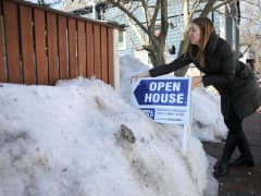 A real estate agent places an Open House sign outside a property in Cambridge, MA.