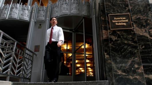 A man exits the American International Building, world headquarters of American International Group (AIG).