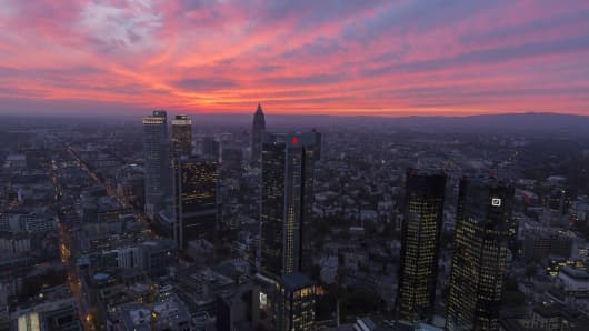 The Deutsche Bank AG logo sits on the bank's headquarters, right, as they stand with other financial center skyscrapers during sunset in Frankfurt, Germany
