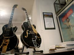 (L-R) Les Paul's 1954 black solid body custom guitar, 'Black Beauty,' and Chet Atkins's 1956 Gretsch black sealed top 6120 prototype, 'Dark Eyes,' seen at Guernsey's auction house in Manhattan, NY, on January 15, 2015. Over 300 guitars are up for auction h