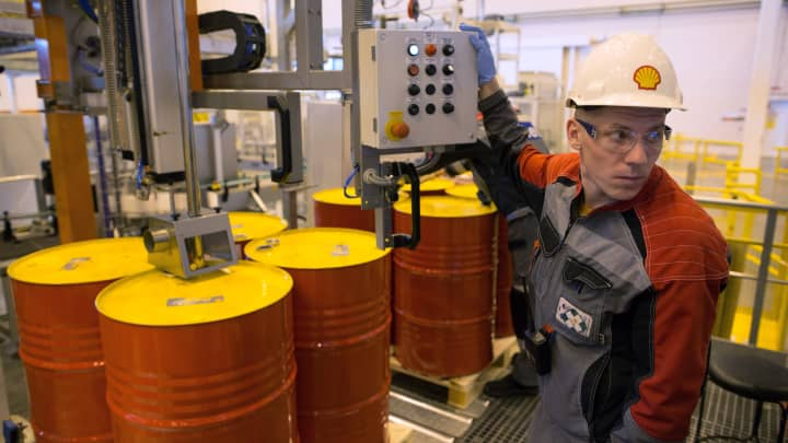 An employee holds a control panel as barrels are filled with lubricant oil ahead of shipping at Royal Dutch Shell Plc's lubricants blending plant in Torzhok, Russia.