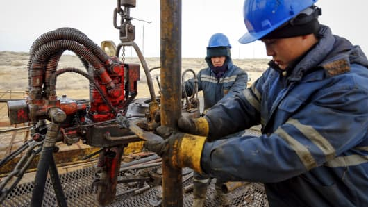 Workers at an oil well operated by a subsidiary of the KazMunayGas Exploration Production JSC in Kazakhstan, January 21, 2016.