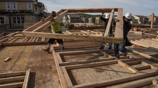 Contractors carry a wall section on a home under construction at the Toll Brothers Inc. Cantera at Gale Ranch housing development in San Ramon, California.