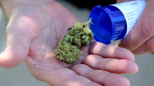 A man displays medical marijuana he picked up from a Massachusetts first medical marijuana dispensary in Salem.
