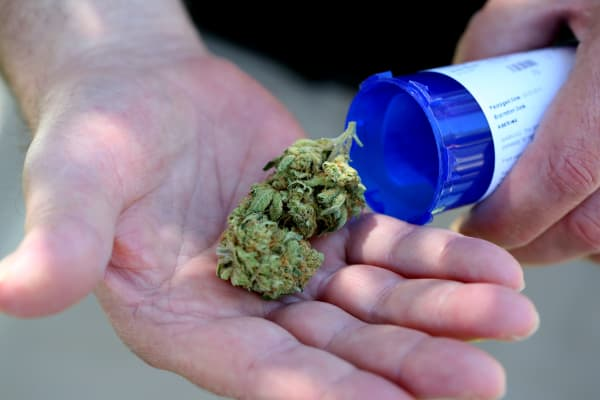 A man displays medical marijuana he picked up from a Massachusetts first medical marijuana dispensary in Salem.