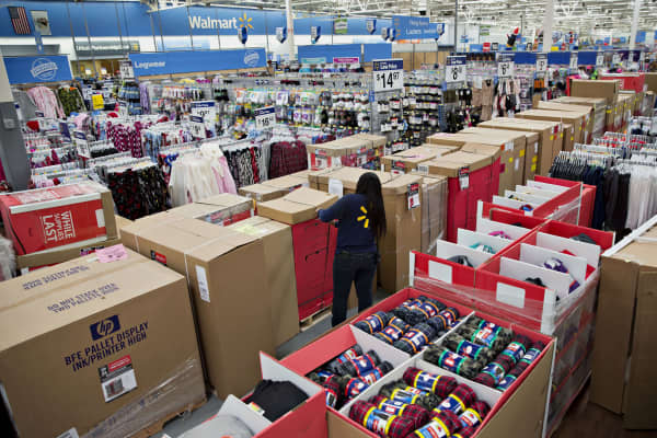 An employee unpacks merchandise in an aisle at a Wal-Mart Stores Inc. location in Chicago, Illinois.