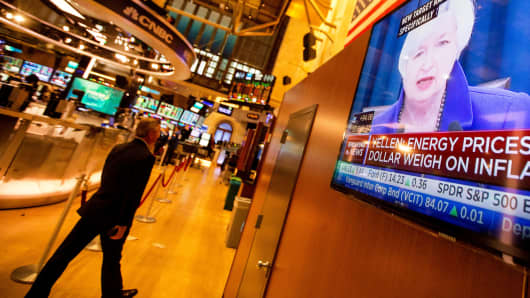 Traders work as Janet Yellen, chair of the U.S. Federal Reserve, is seen speaking on a television screen on the floor of the New York Stock Exchange.