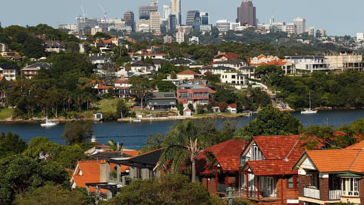 Houses stand by the waterfront as commercial buildings stand in the distance in Sydney, Australia, on Wednesday, Feb. 17, 2016.