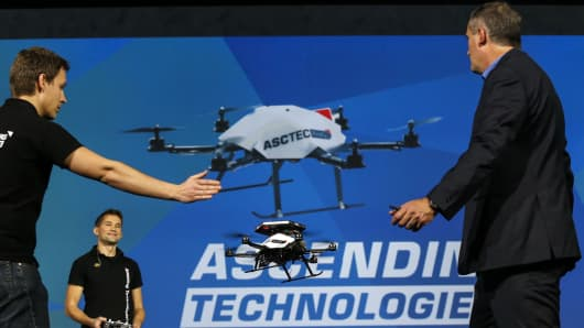 Brian Krzanich, chief executive officer of Intel Corp., right, shows the collision avoidance feature of an AscTec Firefly drone with Intel RealSense cameras during the 2015 Consumer Electronics Show (CES) in Las Vegas, Nevada.