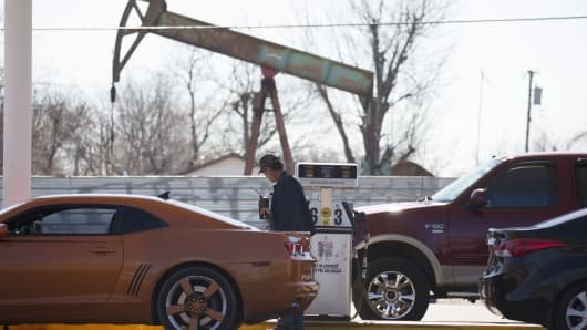 A motorist fills his car with gas at a gas station near an oil field pumping rig in Oklahoma City, Oklahoma.