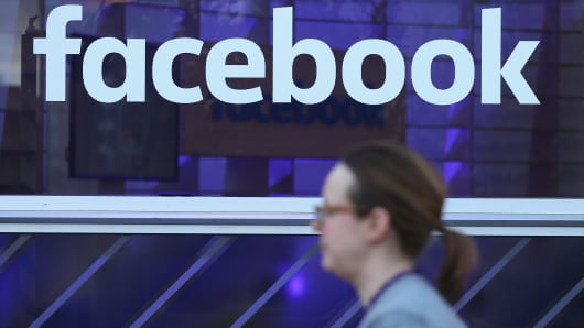 A woman walks past the Facebook logo at the Facebook Innovation Hub on February 24, 2016 in Berlin, Germany.