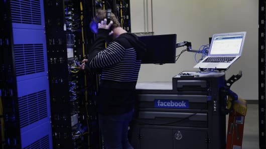An employee fixes part of a web server inside the Facebook Inc. Prineville Data Center in Prineville, Oregon.
