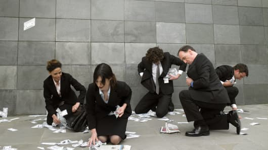 Business people filling pockets and bag with fallen money