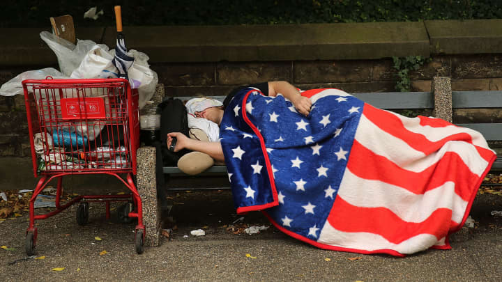 A homeless man sleeps under an American Flag blanket on a park bench on September 10, 2013 in the Brooklyn borough of New York City.