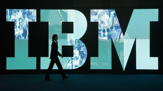 A woman walks past the IBM logo
