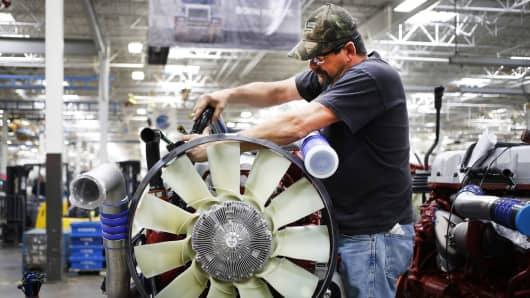 An employee prepares a diesel engine for installation into a truck at the Mack Truck cab and vehicle assembly plant in Macungie, Pennsylvania.
