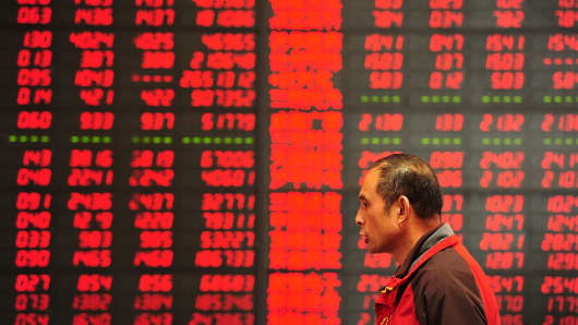 An investor makes his way in front of a screen showing stock market movements in a securities firm in Fuyang, east China's Anhui province.