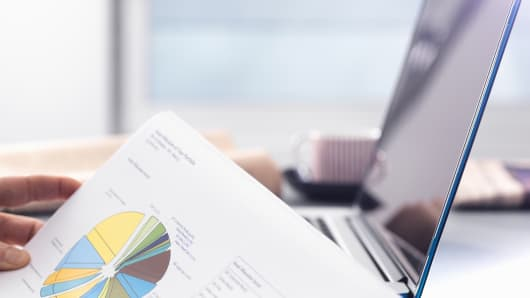 Man reviewing financial affairs using investment statement