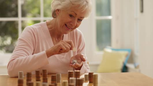Older woman counting coins on a table
