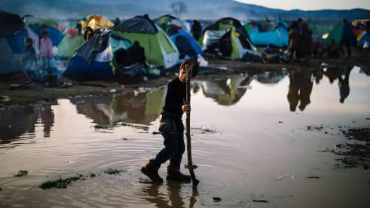 A boy plays in a mud puddle at a makeshift camp of the Greek-Macedonian border near the Greek village of Idomeni, on March 8, 2016, where thousands of refugees and migrants are trapped by the Balkans border blockade.
