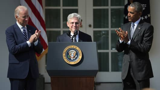 President Barack Obama (R) and Vice President Joe Biden (L) stands with Judge Merrick B. Garland (R), while nominating him to the US Supreme Court, in the Rose Garden at the White House
