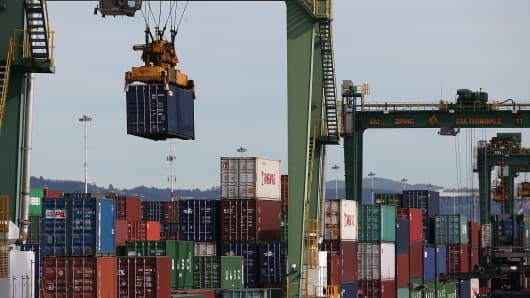 A shipping container is moved with a crane before being loaded onto a ship docked at the Port of Oakland