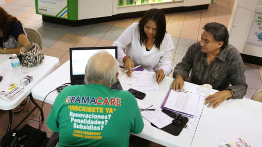 People sit with insurance agents as they discuss plans available under the Affordable Care Act.
