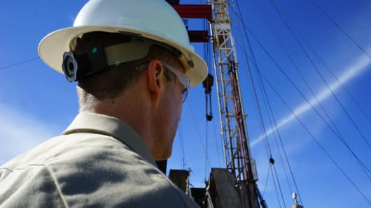 An oil worker stands by a rig near Williston, North Dakota.