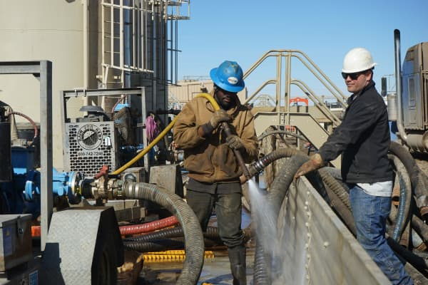 Workers wash off hoses that are part of the oil rig owned by Liberty Resources, located just outside of Tioga, ND in the Bakken region of US.