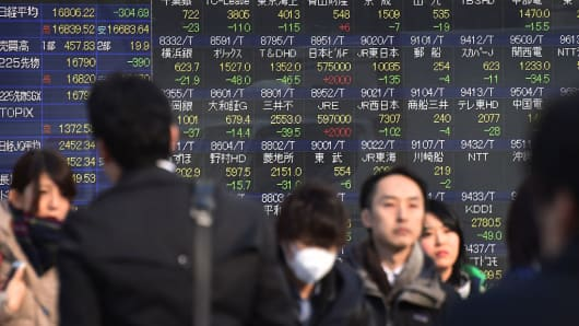 Pedestrians walk past a share prices board displaying movements on the Tokyo Stock Exchange in Tokyo.